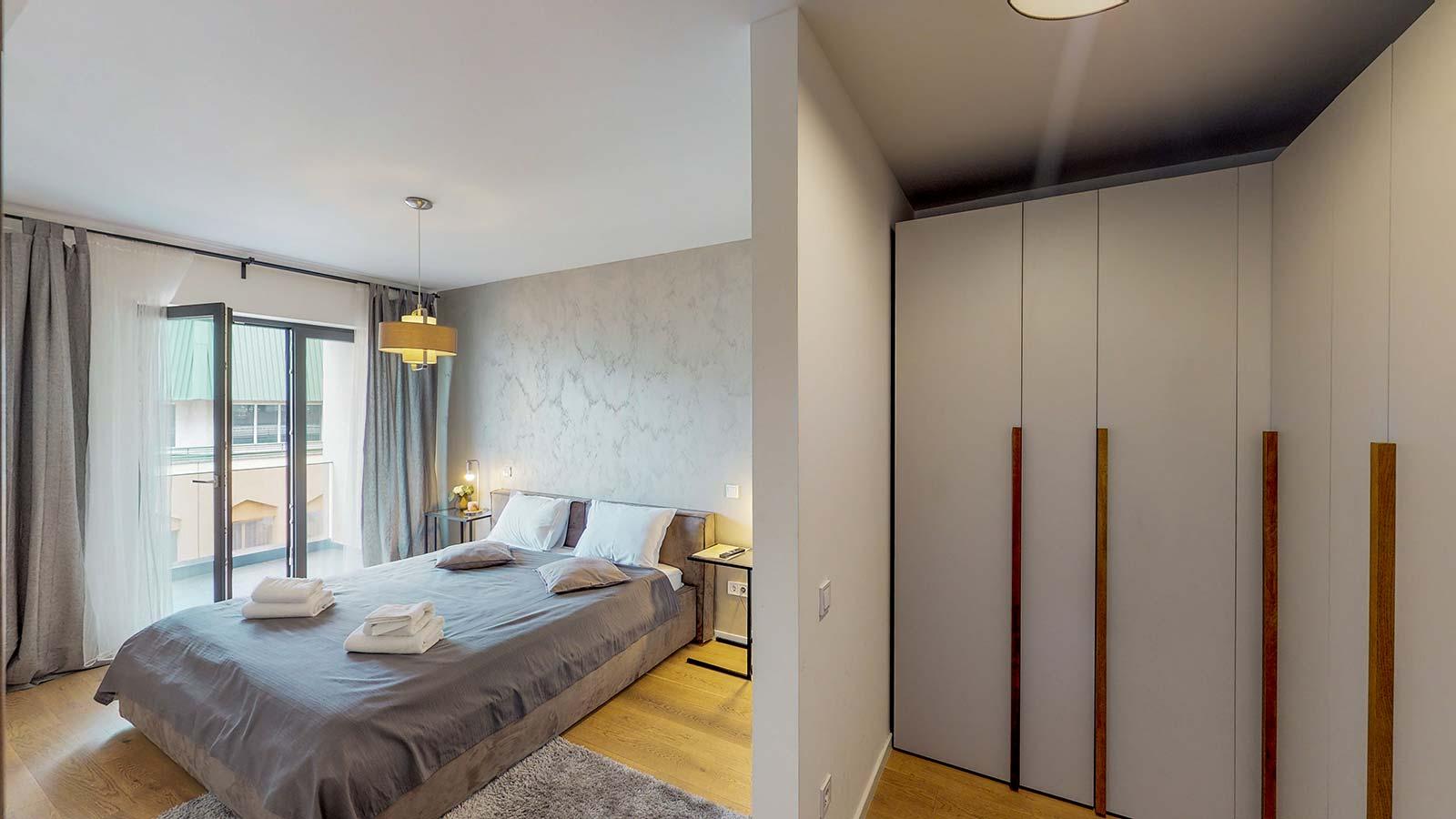 Imagine realizată din hol a dormitorului cu tematică gri şi al dressingului de culoare albă