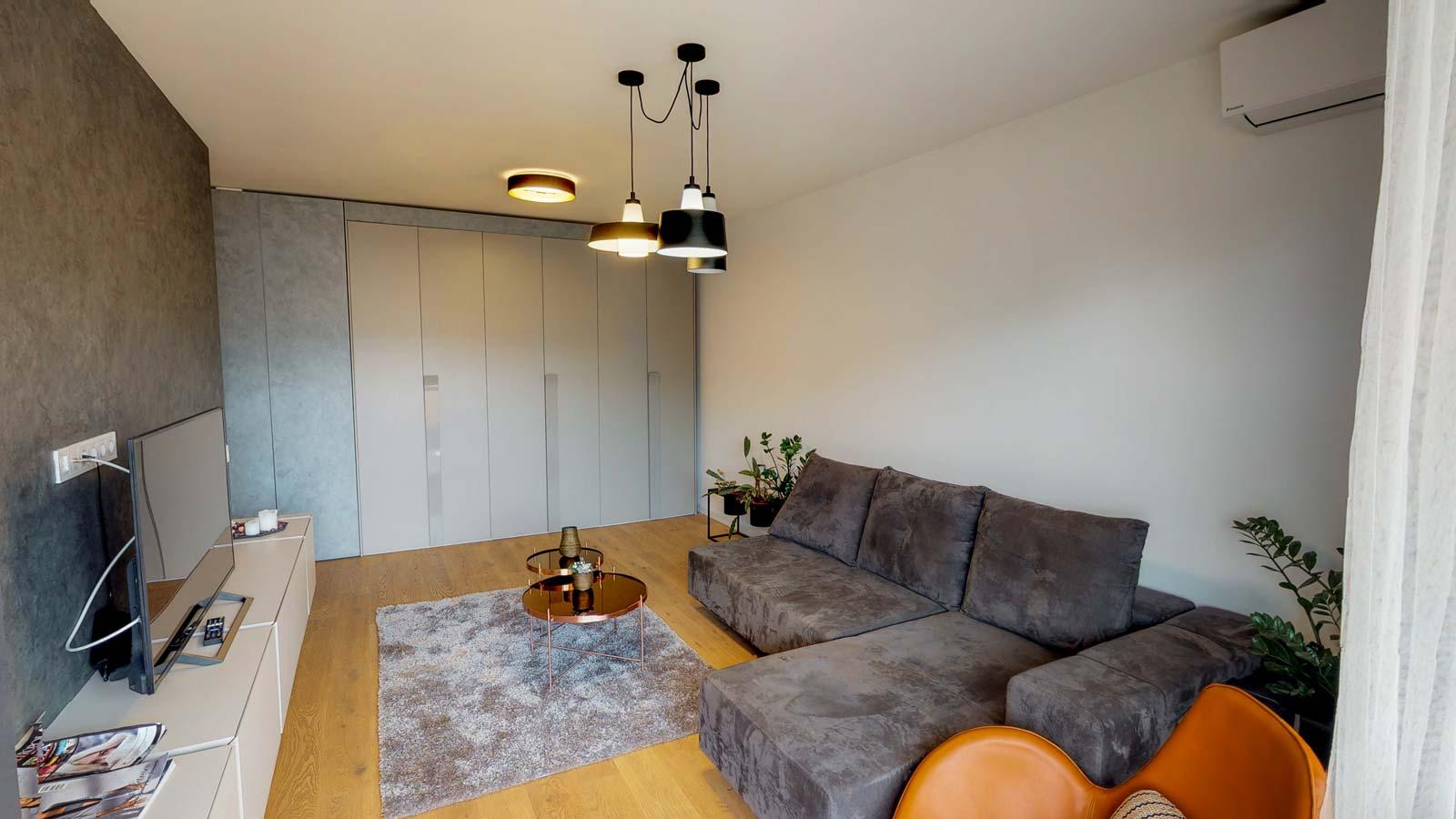 Imagine din sufragerie în care se observă un dulap, o canapea, un mobilier aşezat în faţa canapelei pe care se află un televizor