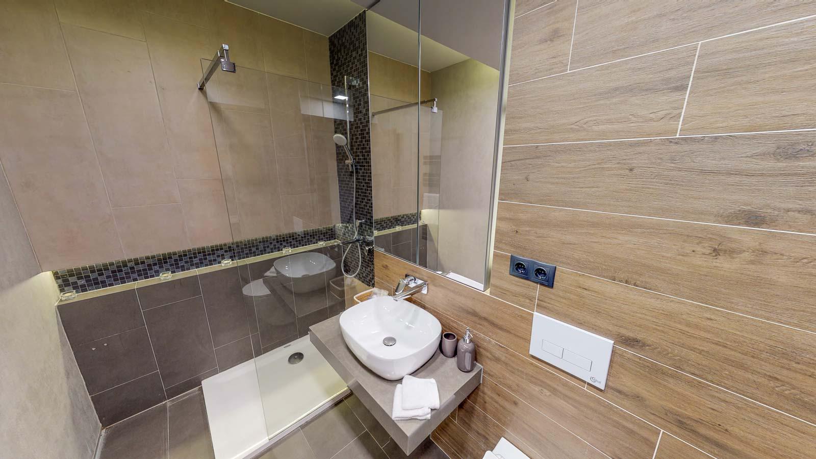 Imagine din baie cuprinzând o oglindă, chiuvetă şi duşul cu paravan de sticlă
