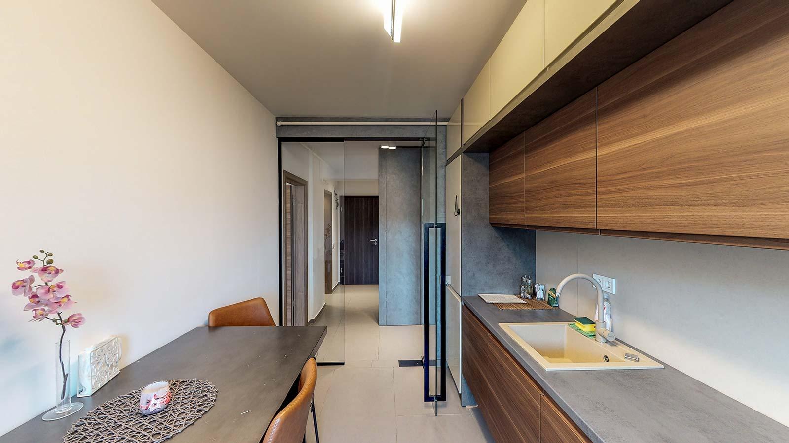 Imagine din bucătărie observându-se chiuveta, masa şi uşa de la ieşire