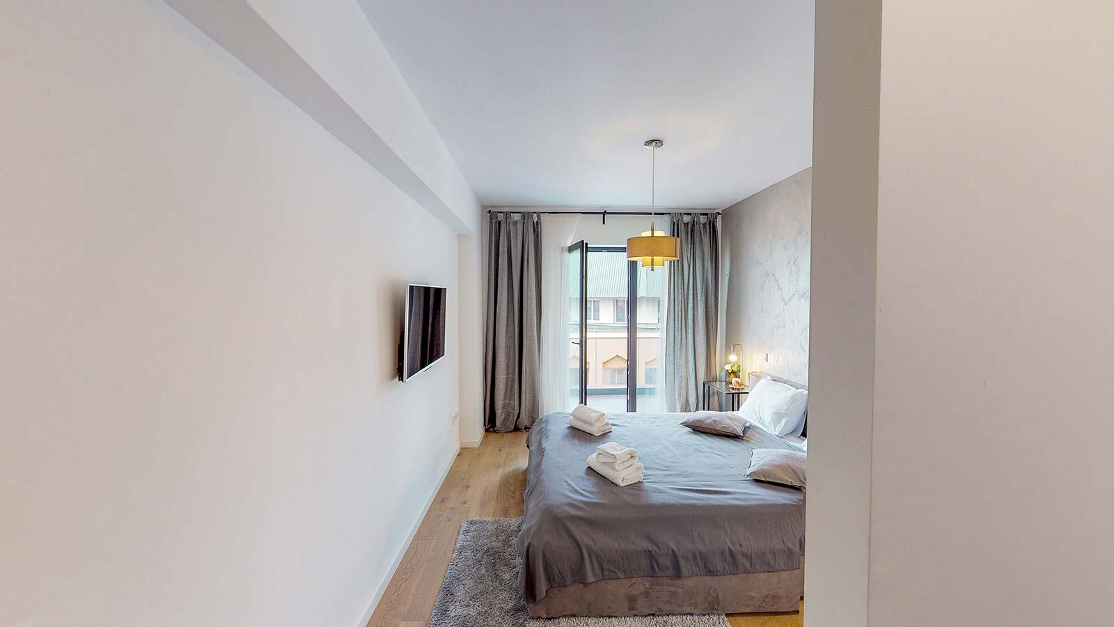 Imagine din dormitor având pereţii de culoare albă şi un televizor suspendat în faţa patului