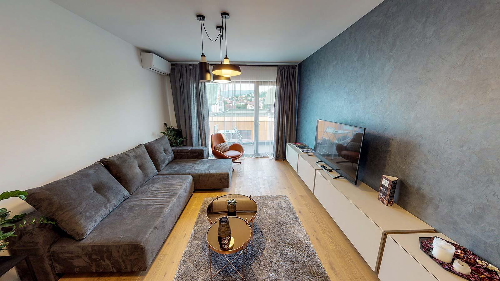 Sufragerie mobilată, în cameră aflându-se o canapea, o masuţa de cafea, un fotoliu şi un dulap în faţa canapelei pe care este plasat un televizor şi câteva obiecte decorative
