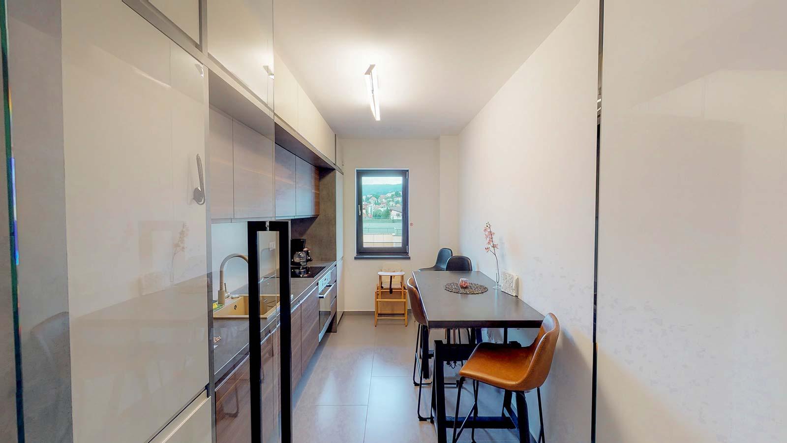 Bucătărie mobilată, îngustă, cu o tematică în culori neutre, preponderent fiind griul