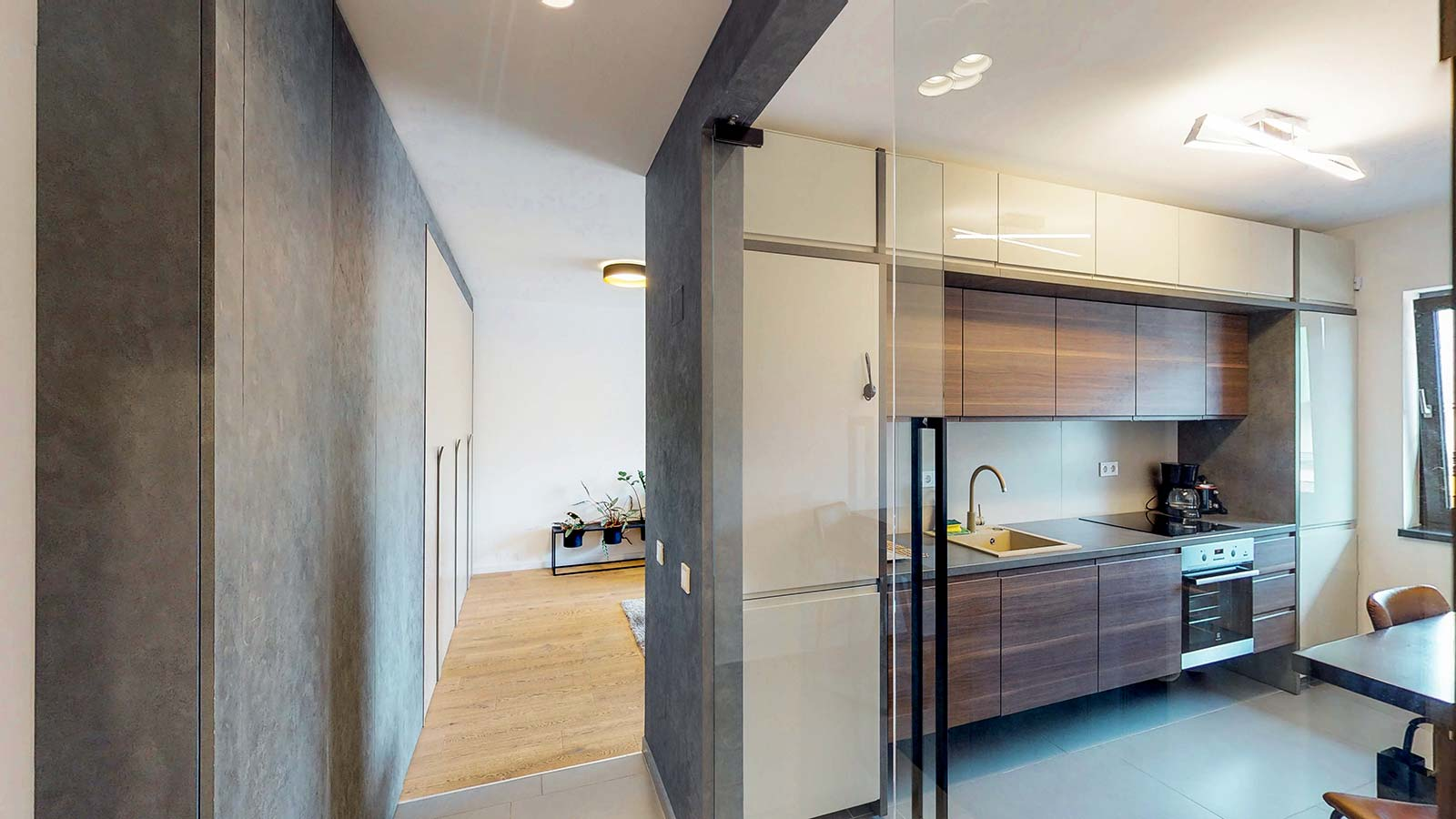 Vedere din hol, în prim plan existând bucătăria spre dreapta apoi spre stânga fiind identificată sufrageria apartamentului