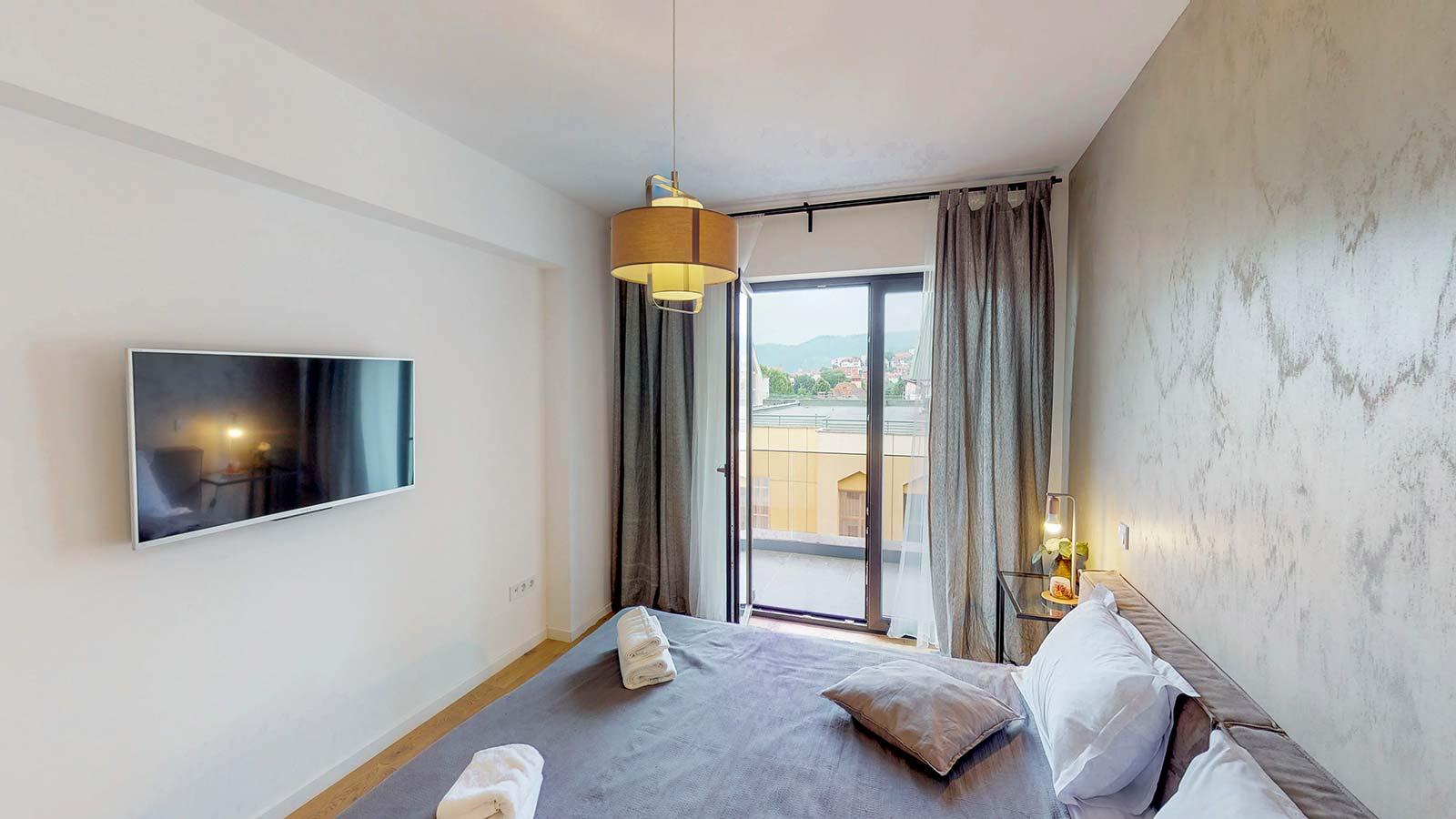 Imagine din dormitor în care se observă întrarea spre balcon, patul, lustra şi televizorul
