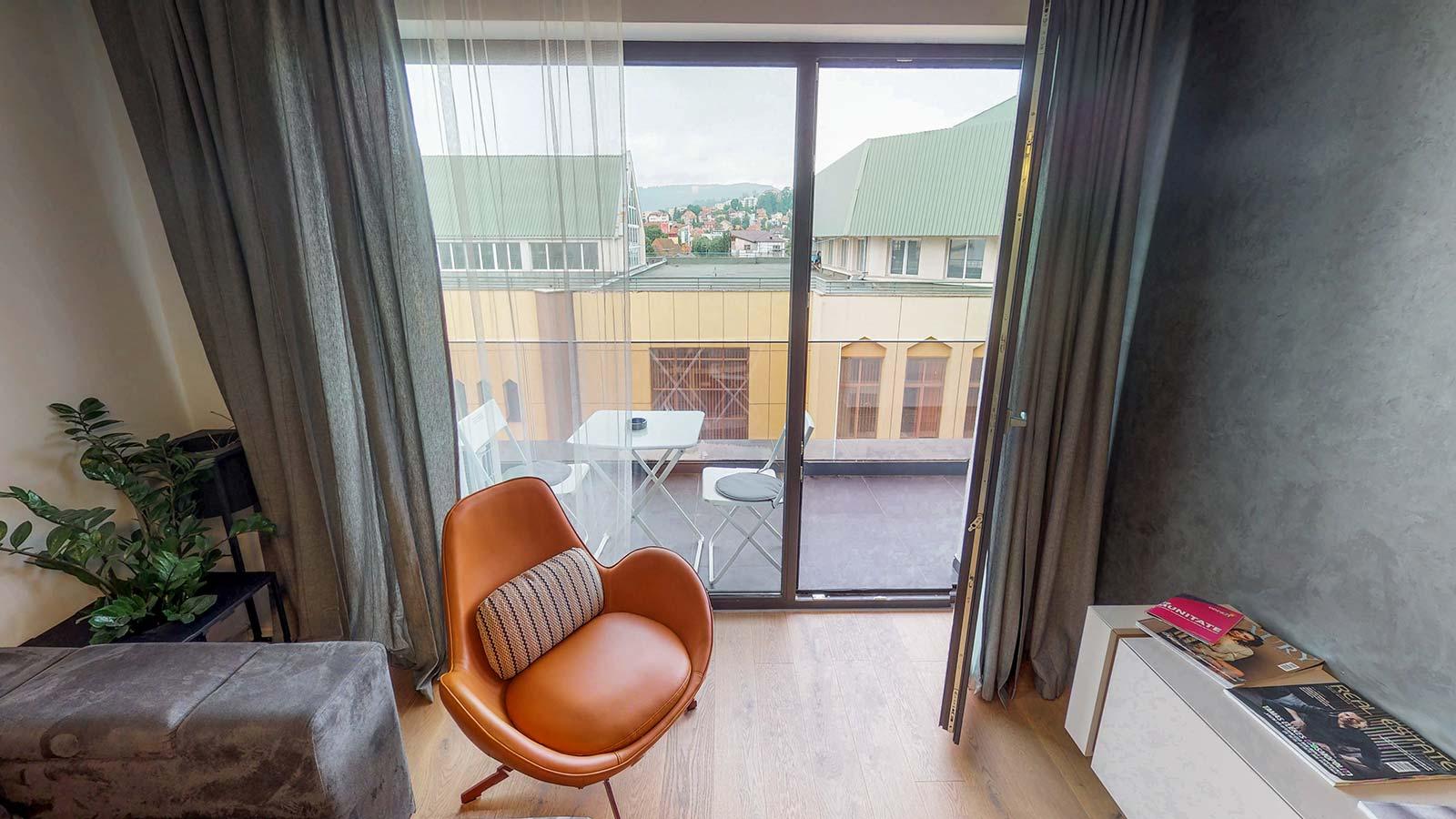 Vedere din sufragerie din care se poate observa balconul pe care este plasată o masă cu 2 scaune
